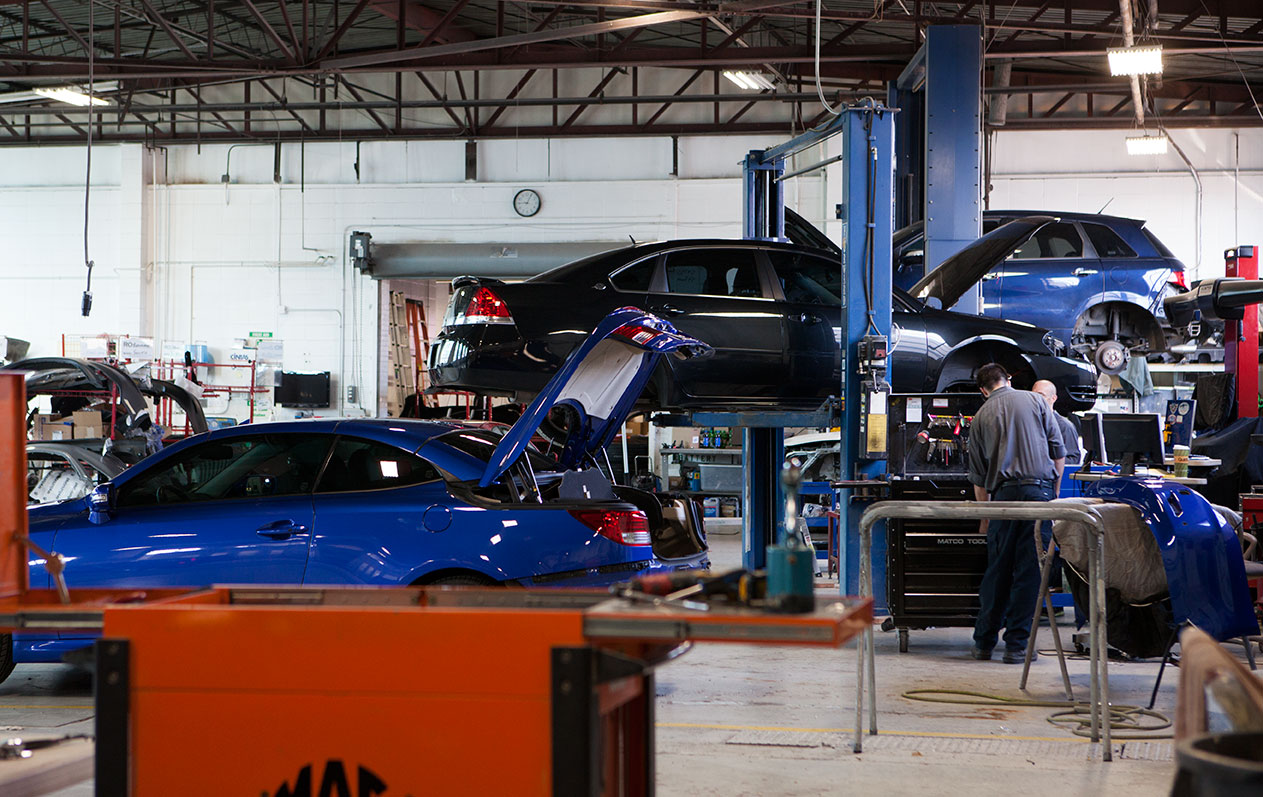 inside schaefer autobody center, people repairing vehicles