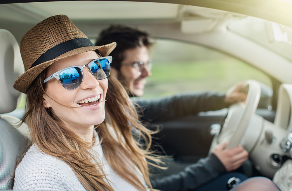 young adults driving in car smiling