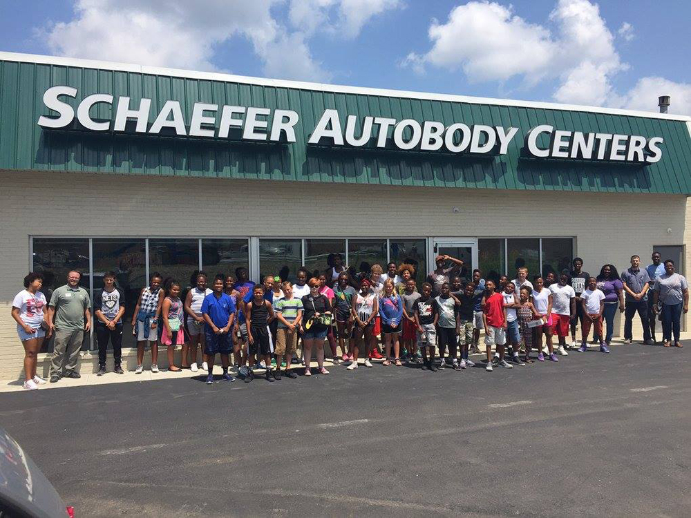 group of kids standing outside schaefer autobody centers location