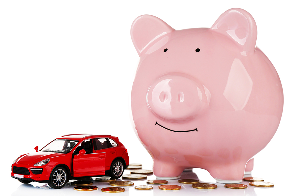 piggy bank next to small toy car surrounded by change