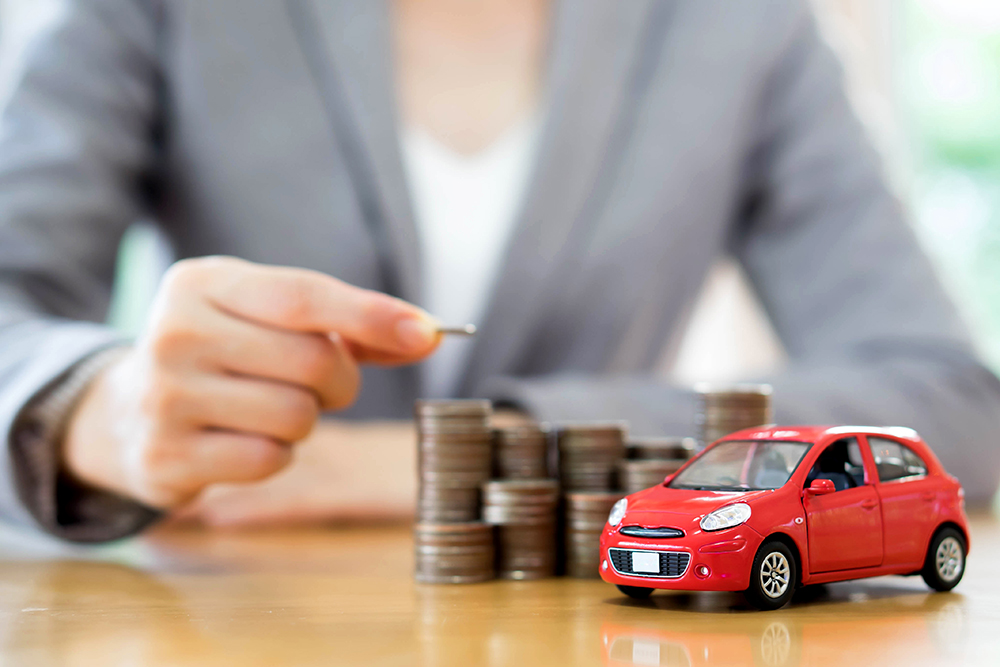 person in blazer stacking change next to toy car