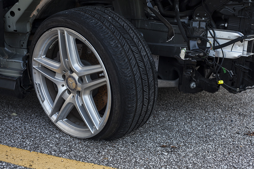 car on road with flat tire and structural damage