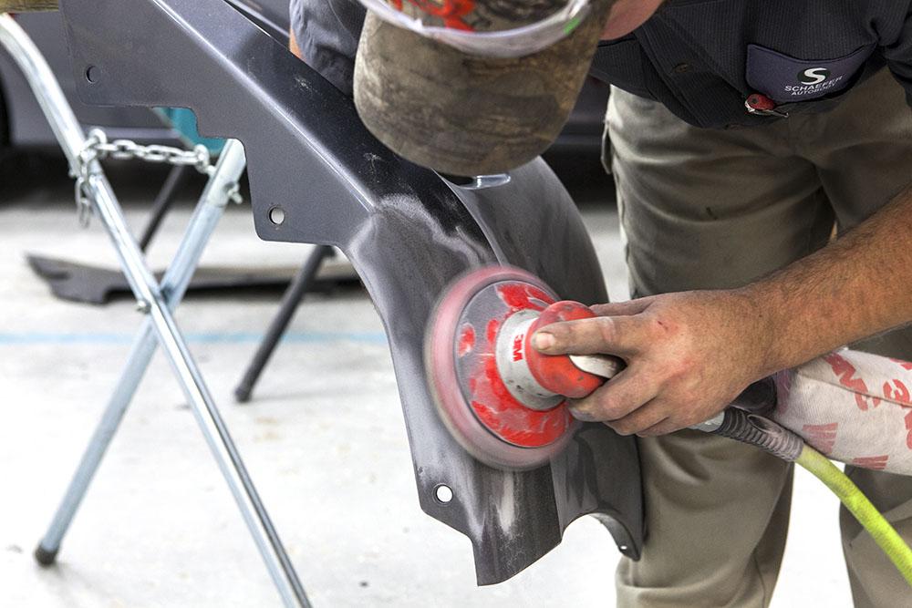 schaefer employee sanding front part of car