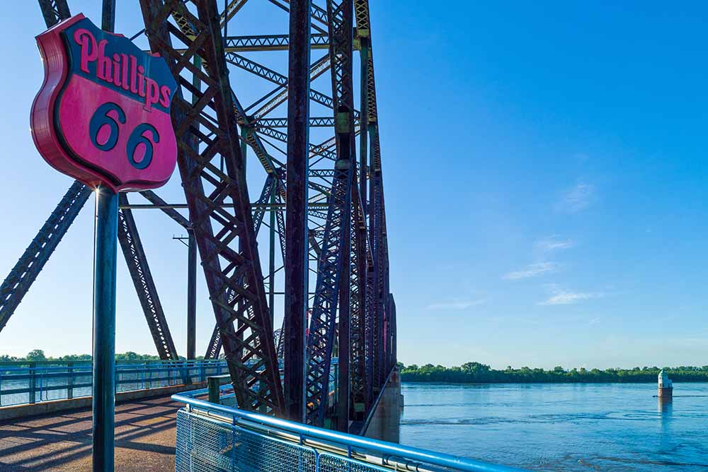 A classic Phillips 66 sign is on display near a St. Louis bridge