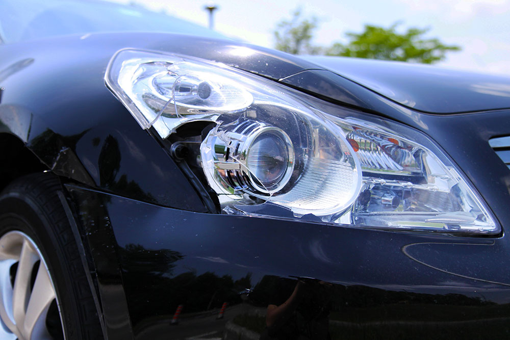 Headlight and body of a black car damaged in collision