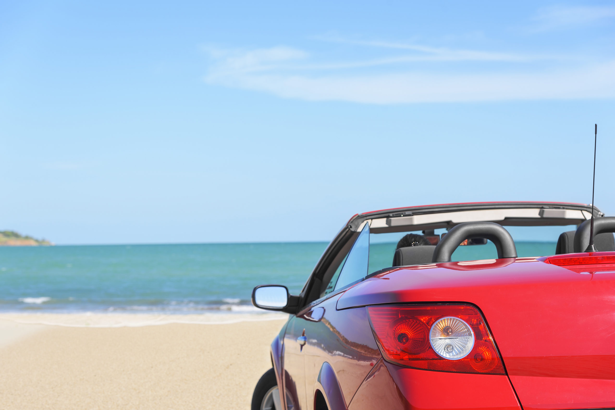 red parked car sitting on beach facing the ocen
