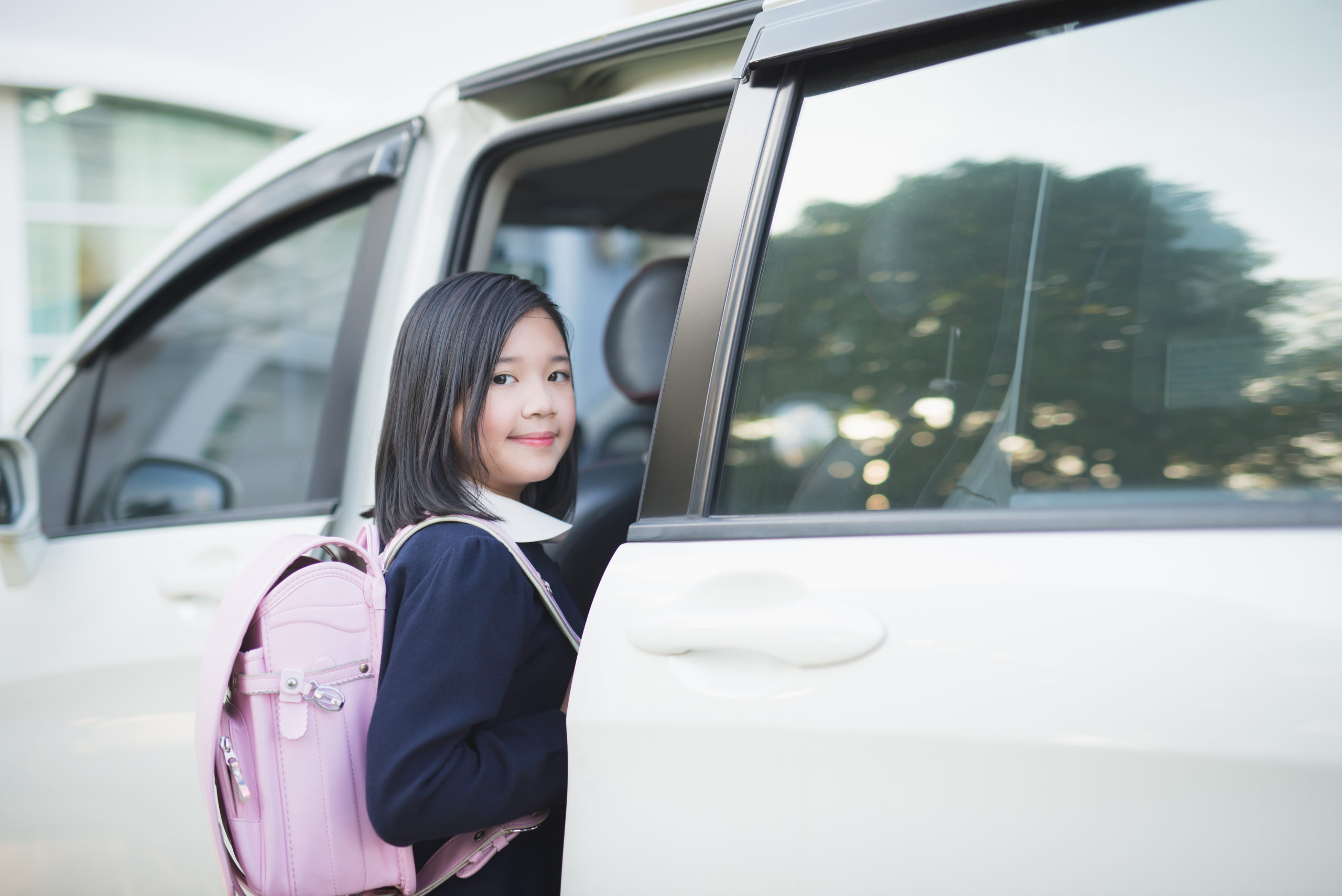 girl in student uniform going to school by car under sunlight