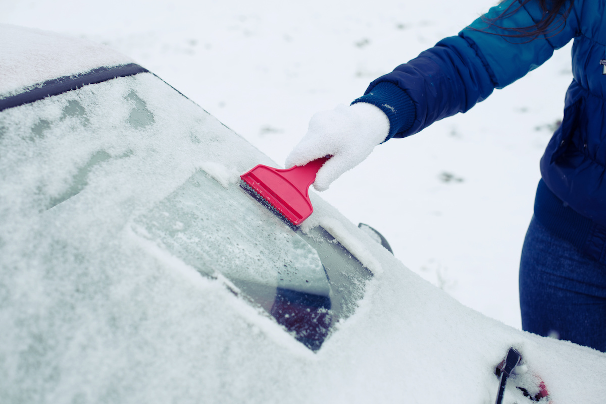 person scraping snow and ice from their car's windshield