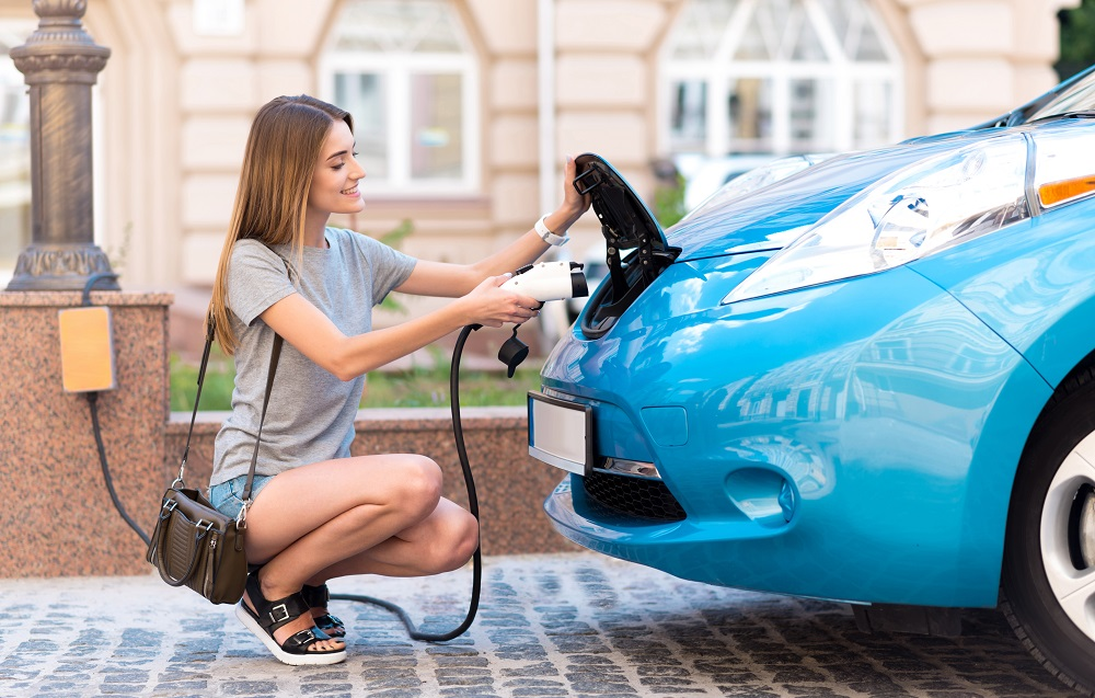 Woman squatting to plug her eco car