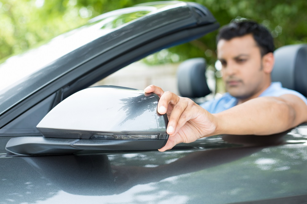 Closeup portrait, young man driver looking adjusting side view car mirror, making sure he can see traffic OK around him, isolated outdoors background