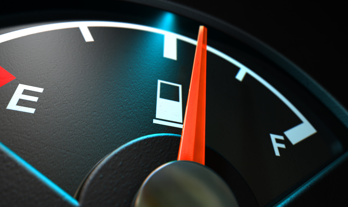 A closeup of a backlit illuminated gas gage with the needle indicating a half full tank on an isolated dark background
