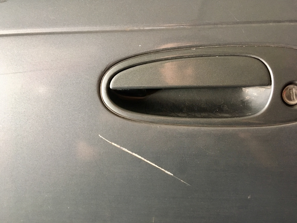 Grazed Scratch on Car - The gray car is scratched by the crashes caused by the careless driving.