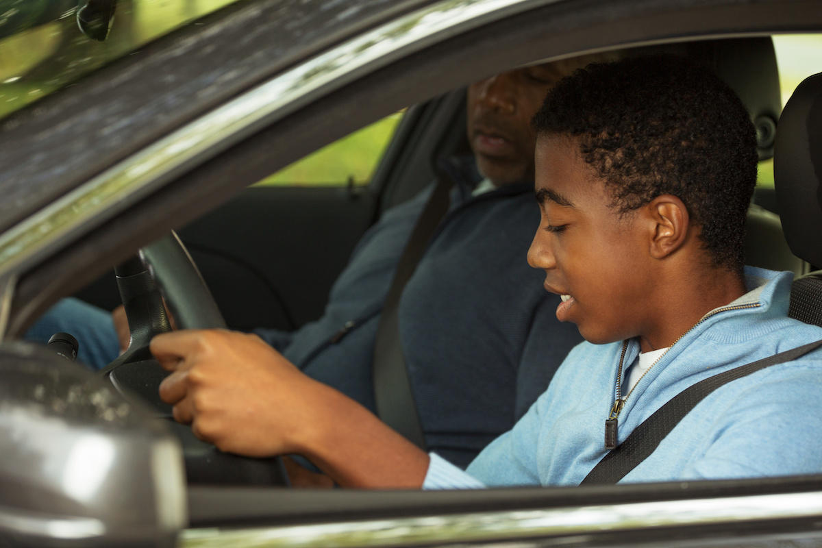 Father teaching his son how to drive.