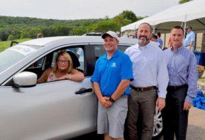 Photo of a woman inside a new car, with Scott Schaefer standing beside the car.