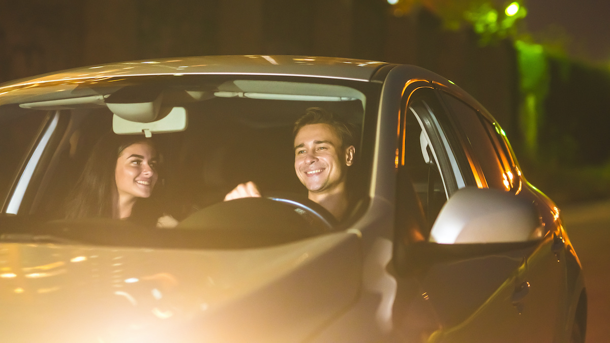 happy man and woman drive a car at night time