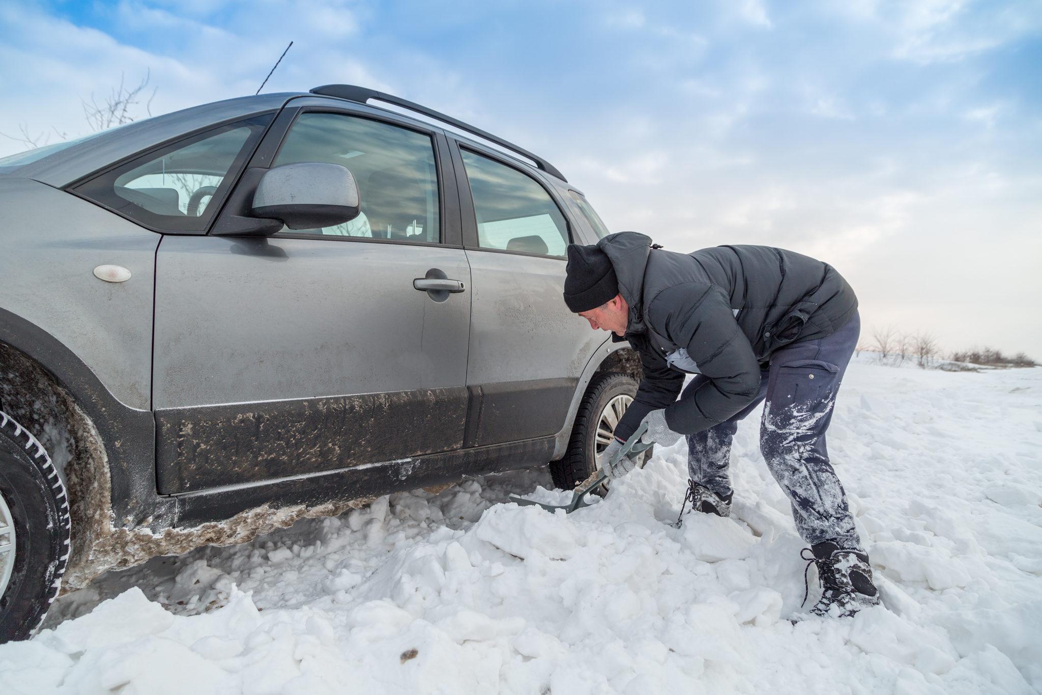 man shoveling snow to free his stuck car