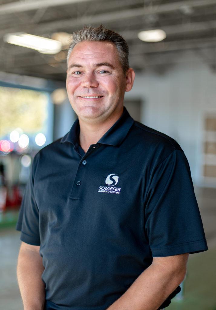 Scott Schaefer, owner of Schaefer Autobody, smiling in Schaefer polo shirt.