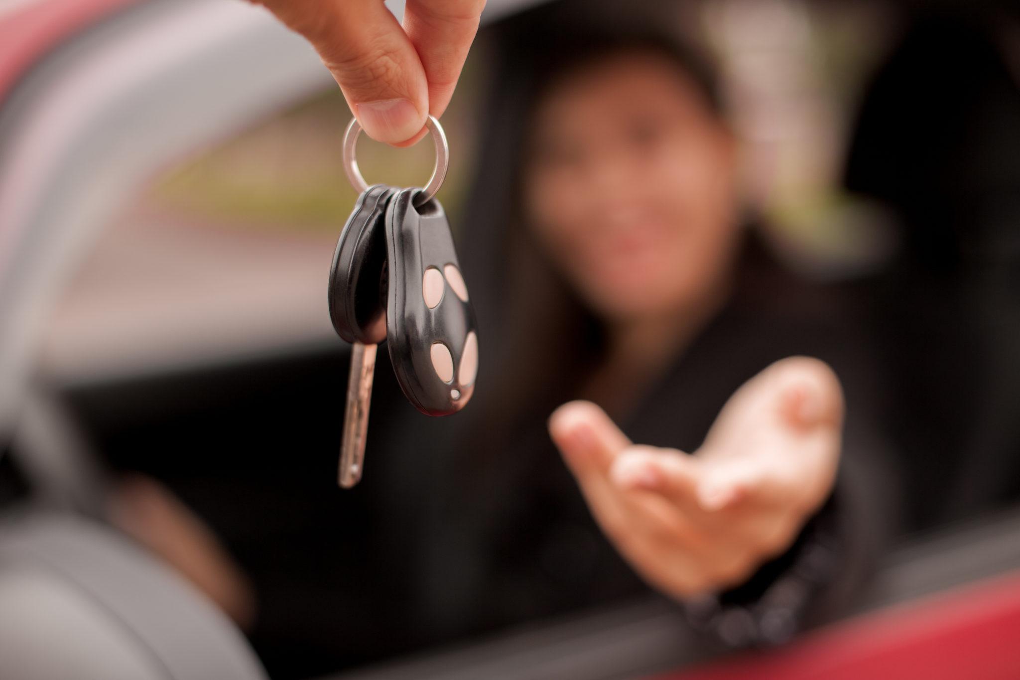 showroom dealer gives car keys to the buyer
