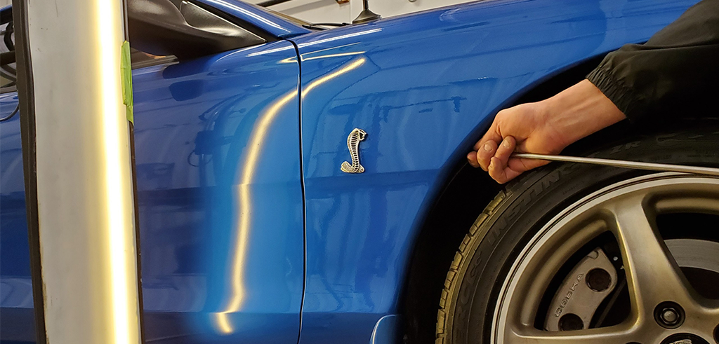 Hand reaching into frame to remove dent from a blue sports car