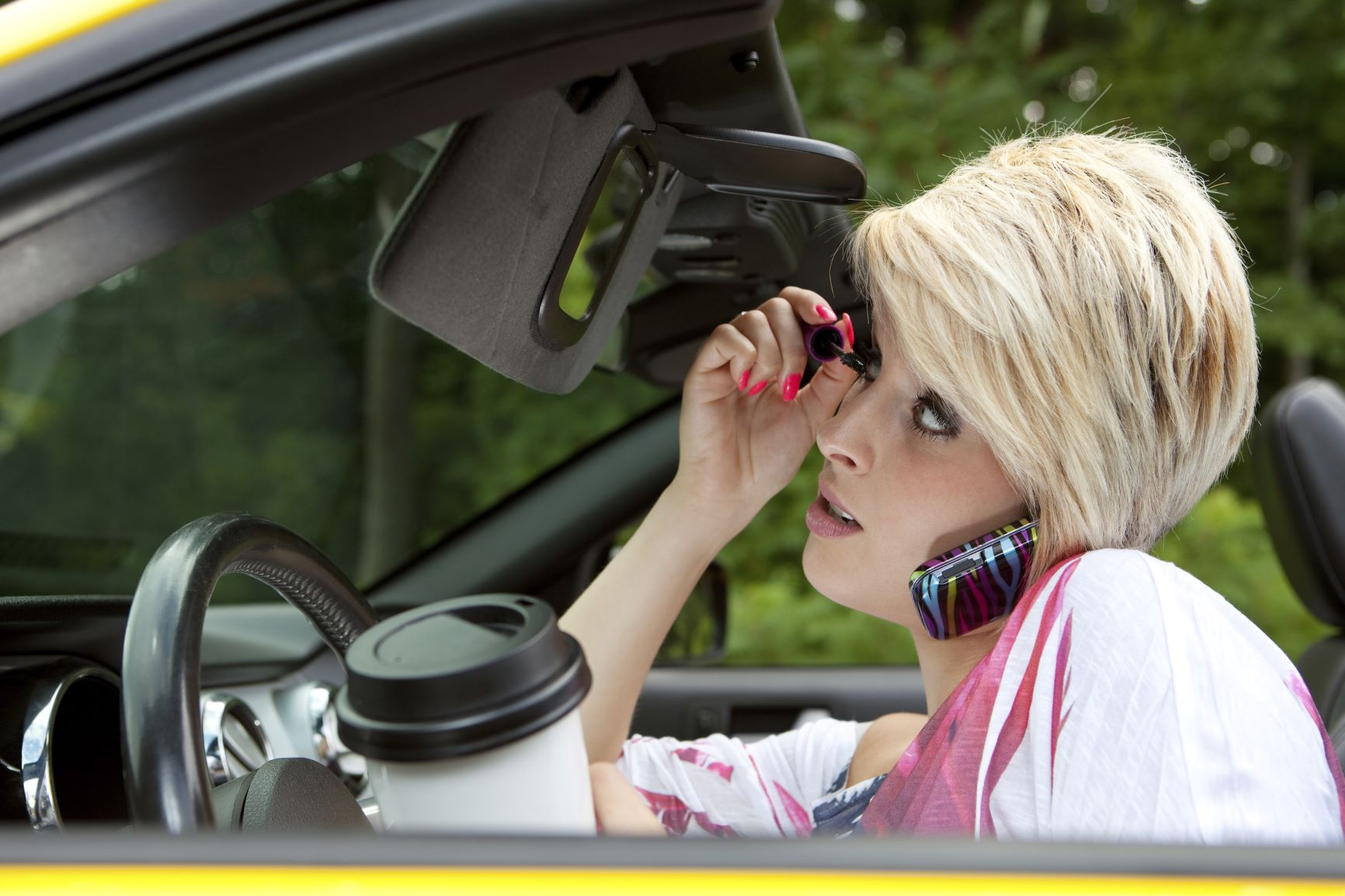 woman driving car while applying mascara, talking on her phone, and holding a coffee