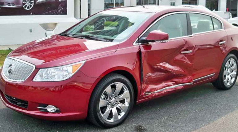 Before shot of a red Buick that had sustained major damage to the driver's side.