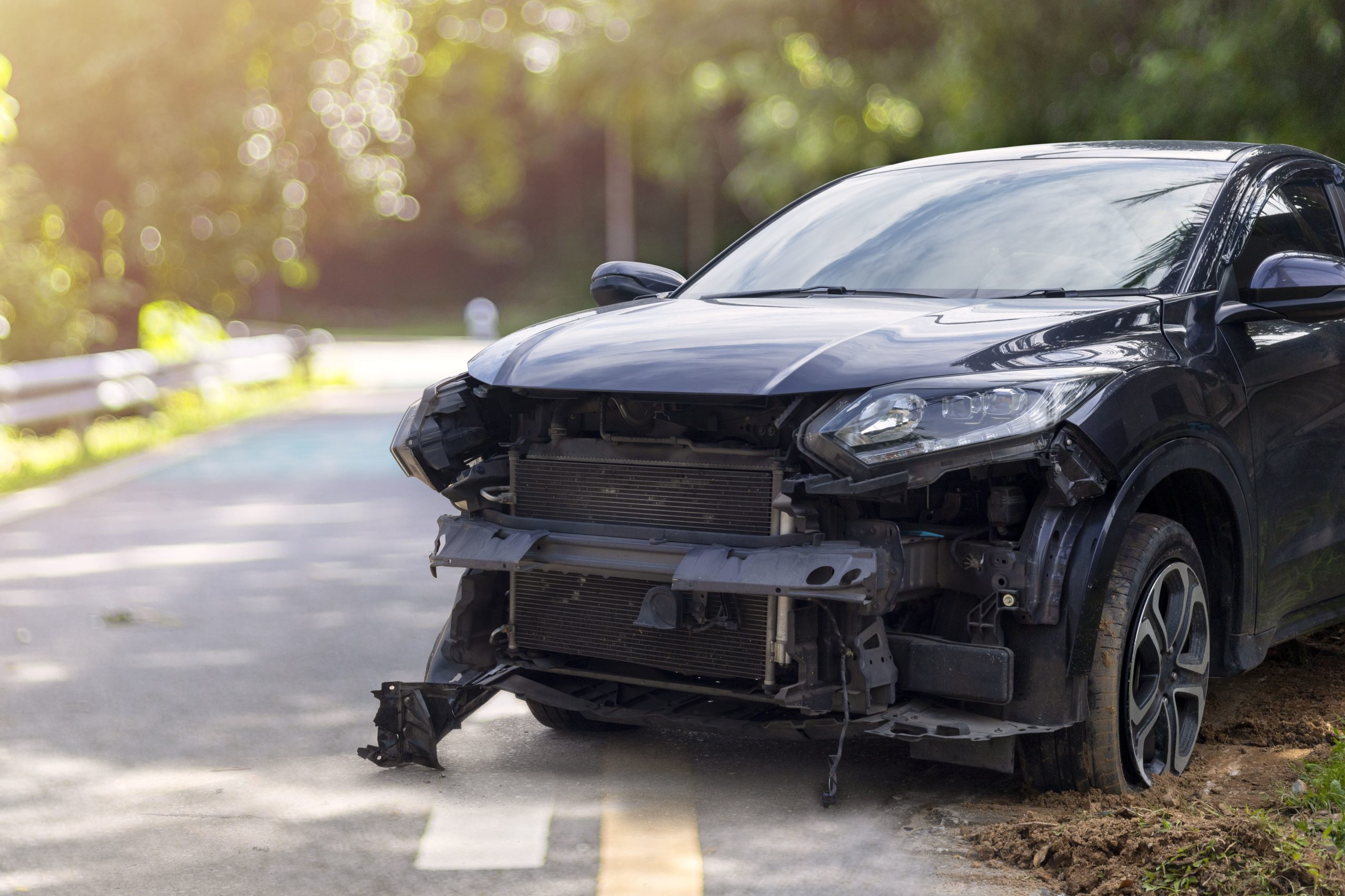 black car on side of road with damaged front